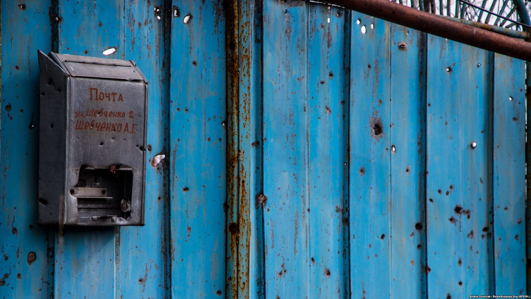 Вулиця Шевченка, 2, жив Шевченко А.Г. На фото – посічені осколками ворота до подвір'я в центрі села. Вказувати біля адреси ще й прізвище господаря – це була місцева традиція