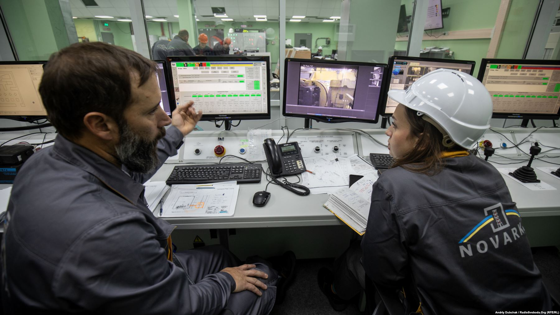 Two nuclear containment specialists inside the main control center at the New Safe Confinement (NSC). Some 3,000 people work at the site, including several foreign specialists. Photo by: Andriy Dubchak