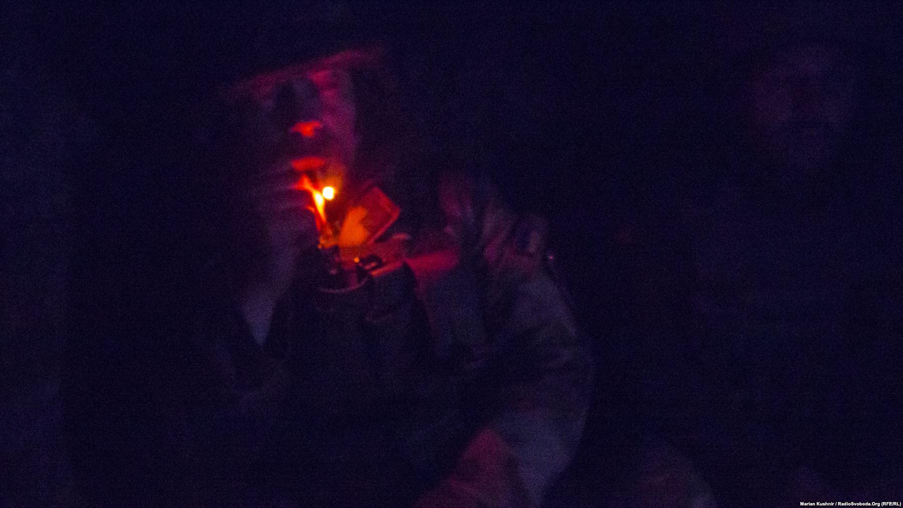 Михайло курить у суцільній темряві бліндажа під час спостереження на передових позиціях