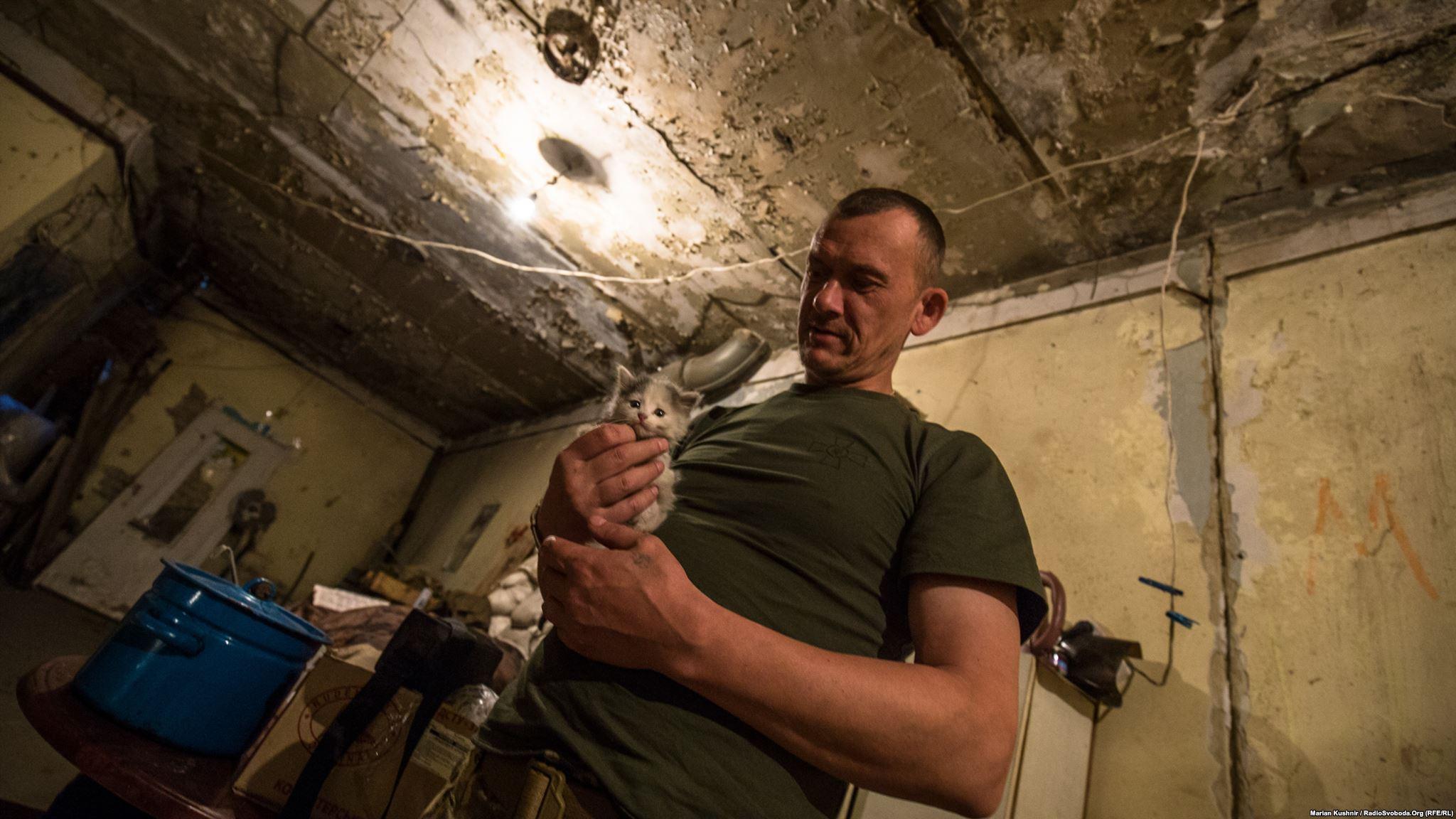 Вояк з позивним «Колесо» показує нам одне з нещодавно народжених кошенят. Ці позиції «котячі», тут майже немає собак. Ще розповів, як нещодавно снайперська куля влучила прямісінько в цівку його кулемета. Результат – перебита цівка, зброя вийшла з ладу. Солдат тішиться: «Вчасно відійшов із лінії вогню і залишився живим» (ukraine conflict photographer Andriy Dubchak)
