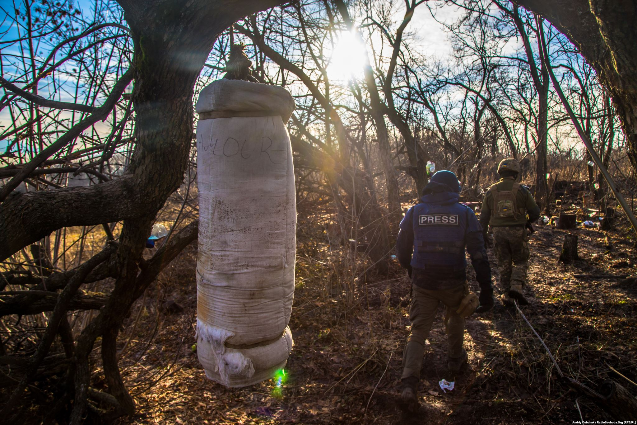 Hand-made punch bag in a wood lane. Near that improvised sports ground between trees, there are many mine craters. We also saw the remnants of an unexploded rocket-propelled grenade.) (photo by ukrainian military photographer Andriy Dubchak)