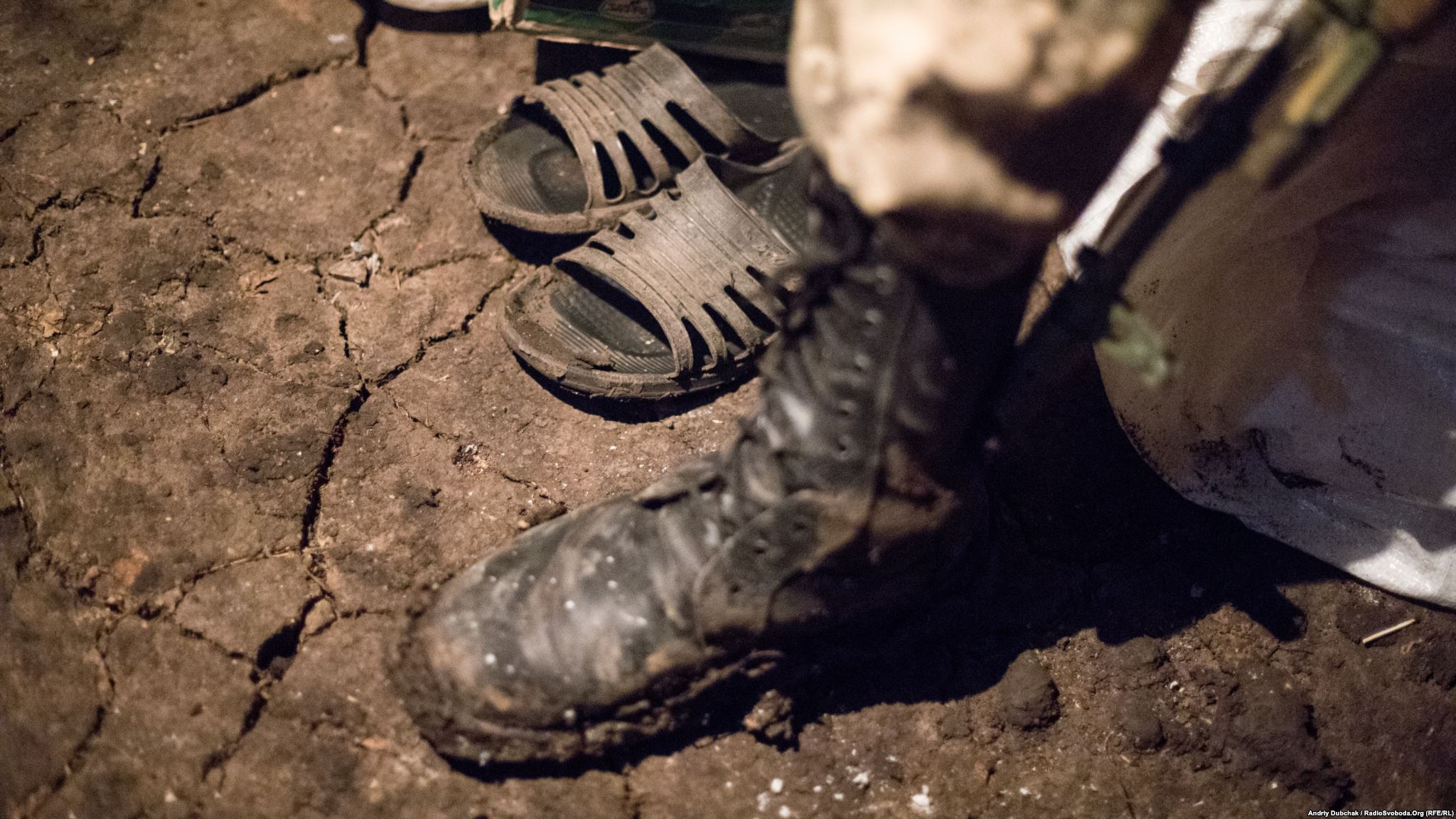 An earthen floor and home slippers can be seen in one of the inhabited dugouts on frontline (photo by ukrainian military photographer Andriy Dubchak)