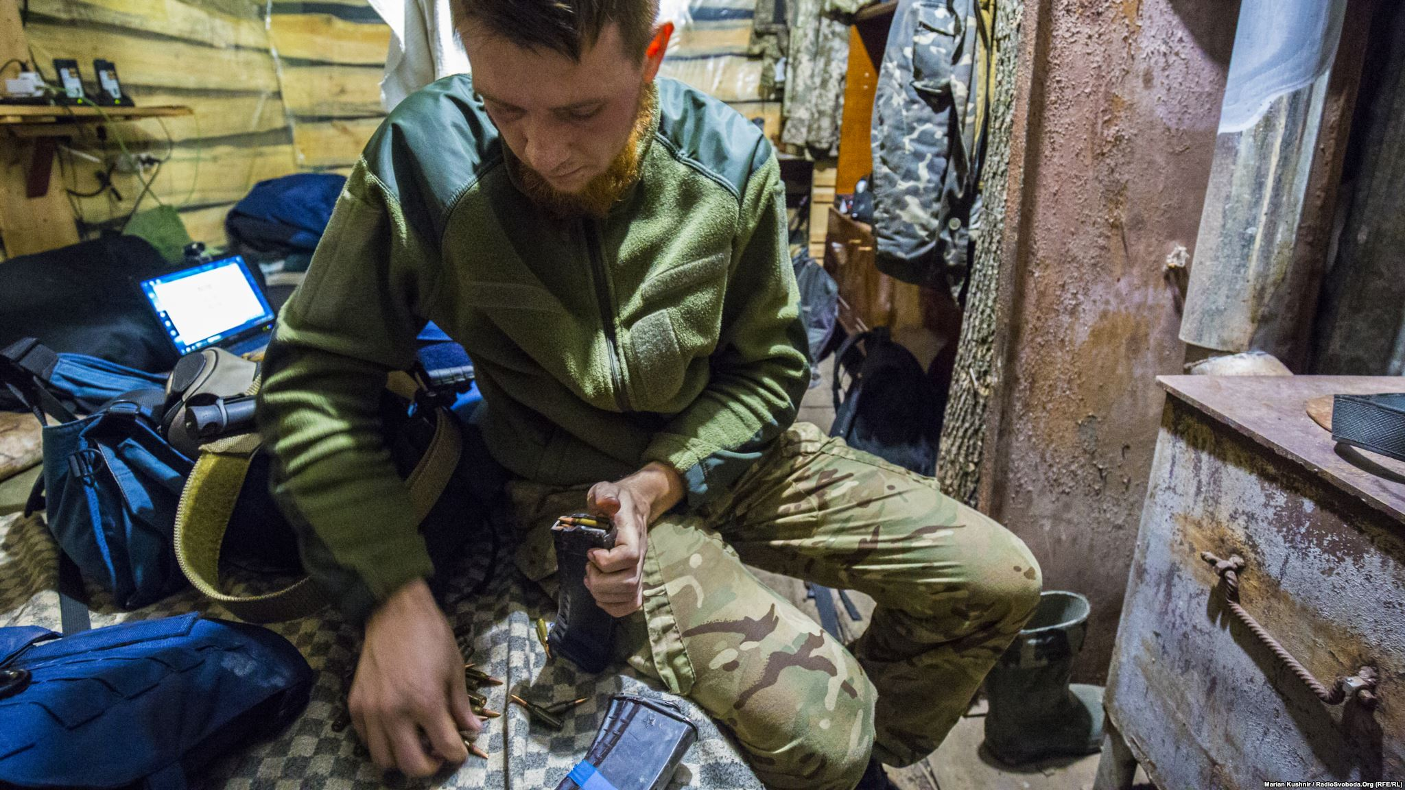 Yevhen loads rounds to assault rifle's magazine before going to the frontline with us