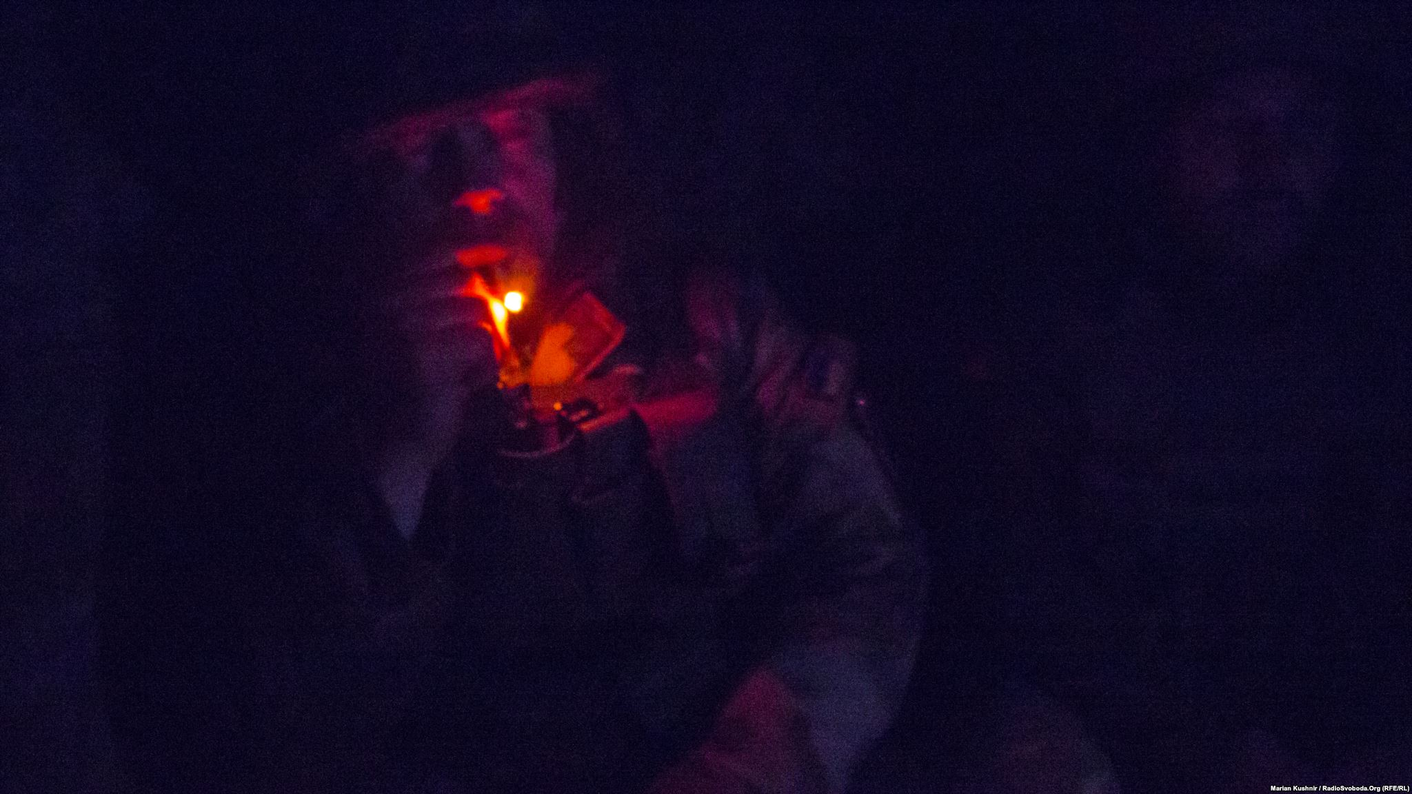 In total darkness of a dugout, Mykhajlo smokes while on watch in frontline positions