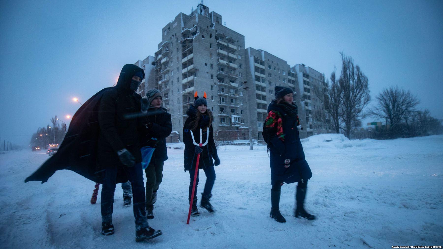Діти колядники йдуть повз зруйновані війною будинки у Авдіївці. Фото - Андрій Дубчак